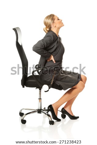 Young businesswoman having back pain - stock photo