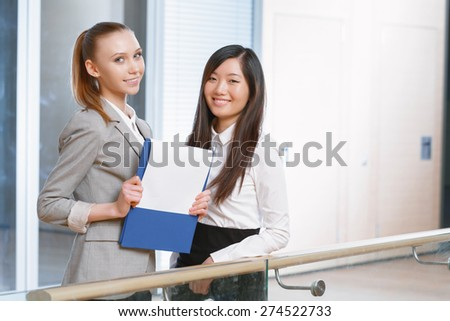 Young businesswoman holding a folder and smiling with her colleague in the office - stock photo