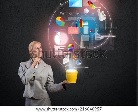 Young businesswoman holding bucket with graphs and diagrams flying out - stock photo
