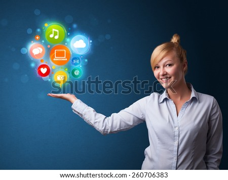Young businesswoman holding colorful multimedia icons in her hand - stock photo
