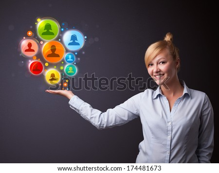 Young businesswoman holding colorful social network icons in her hand - stock photo