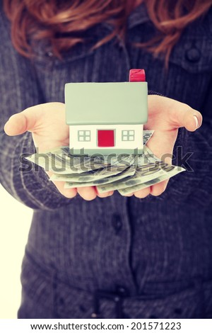 Young businesswoman holding euros bills and house model over white - real estate loan concept - stock photo