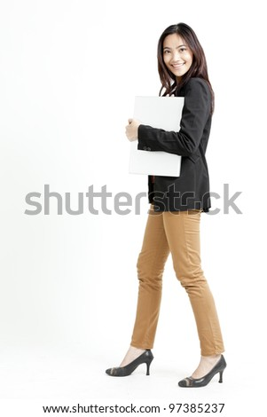Young businesswoman holding her laptop on isolated background - stock photo