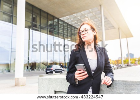 Young businesswoman holding her smart phone and looking away from camera. The woman looks focused and resolute. Modern building on background - stock photo