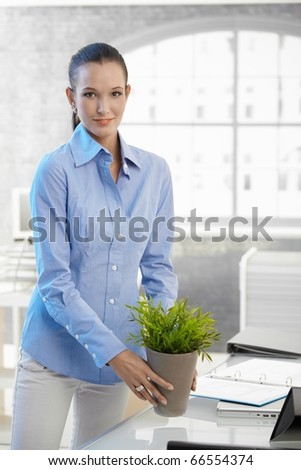Young businesswoman holding potted plant standing at office desk, smiling at camera.? - stock photo