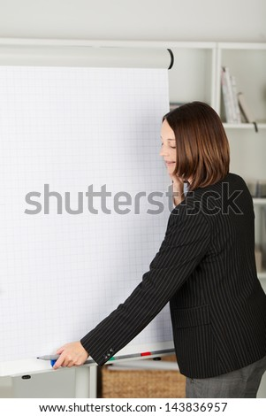 Young businesswoman in a black jacket starting a presentation in office - stock photo