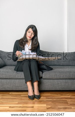 Young businesswoman in a stylish slack suit sitting on a sofa reading her notes or paperwork in an office binder with an expression of concentration - stock photo