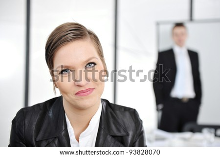 Young businesswoman in business meeting at office, looking at camera smiling - stock photo