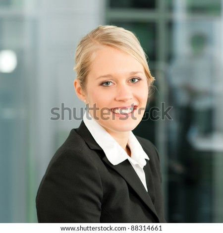 Young businesswoman in her office; she is looking into the camera - stock photo