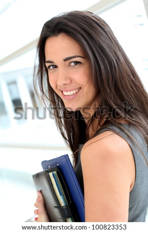 Young businesswoman in modern building holding files - stock photo