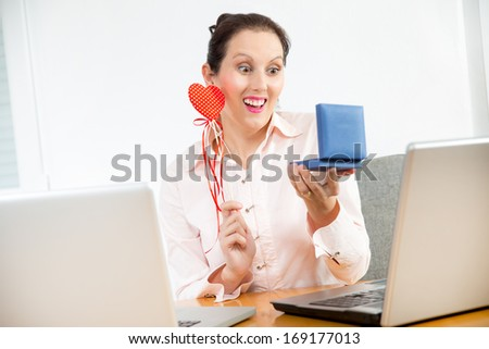 young businesswoman in office with valentines hearts and gift bo - stock photo