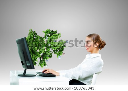 Young businesswoman in the office with money banknotes around her - stock photo