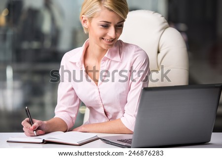 Young businesswoman is working with laptop at office. - stock photo