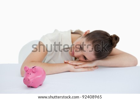 Young businesswoman leaning on her desk with a piggy bank against a white backgroun - stock photo