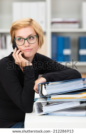 Young businesswoman listening to a mobile phone call looking up into the air with a bored disbelieving expression as though she has heard it all before - stock photo