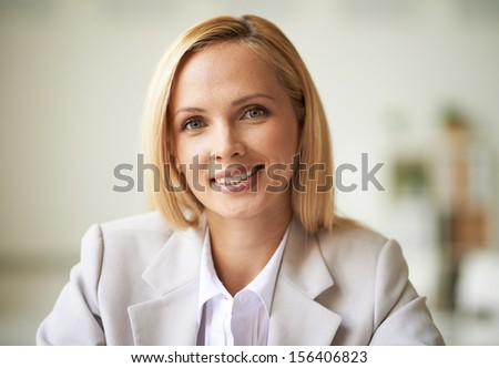 Young businesswoman looking at camera with toothy smile - stock photo