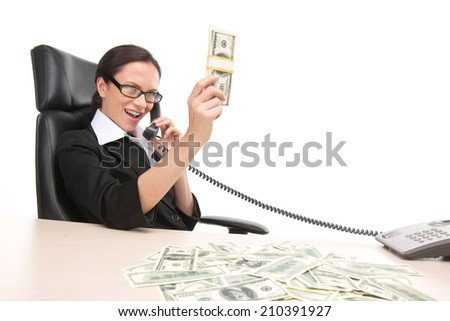 Young businesswoman looking at money scattered on table. happy and excited woman sitting at the table covered with money and talking on phone - stock photo