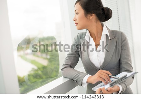 Young businesswoman looking at the window - stock photo