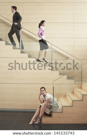 Young businesswoman looking away while using cellphone with colleagues climbing stairs in office - stock photo