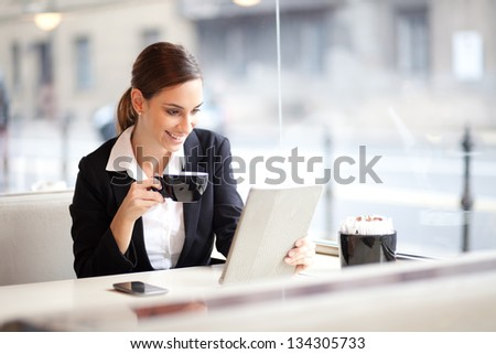 Young businesswoman on a coffee break. Using tablet computer. - stock photo