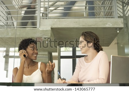 Young businesswoman on call with female colleague noting down at table - stock photo