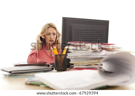 Young businesswoman on cell phone at desk - stock photo