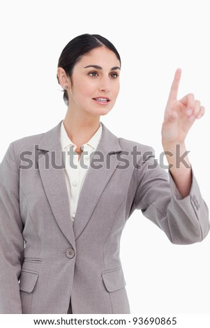 Young businesswoman operating touch screen against a white background - stock photo