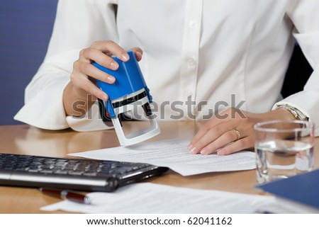 Young businesswoman (or notary public) sitting at the desk in office and stamping document - stock photo
