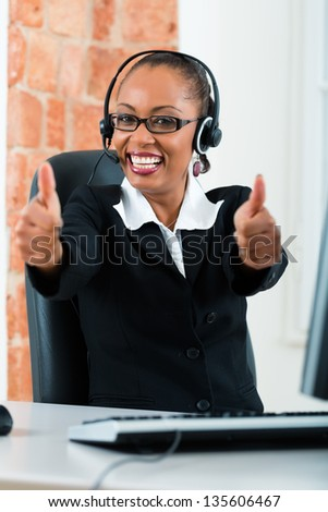 Young businesswoman or secretary working in her Office, she sitting on the desk in front of the window and working on a computer with a headset, she has a customer pitch - stock photo