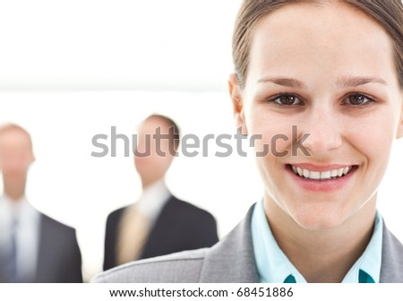Young businesswoman posing in front of two businessmen standing on the background - stock photo