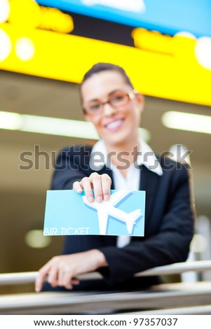 young businesswoman presenting air ticket at airport, focus on foreground - stock photo