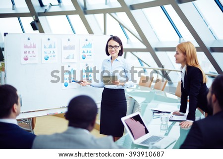 Young businesswoman presenting financial statistics to her partners at conference - stock photo