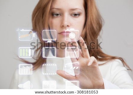 Young businesswoman pressing high tech type of modern multimedia buttons on a virtual background - stock photo