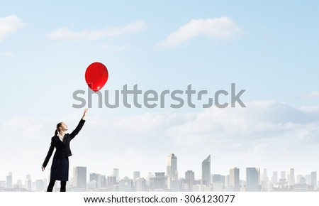Young businesswoman reaching hand to touch balloon in sky - stock photo