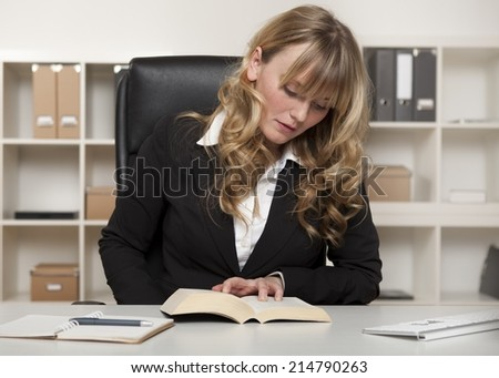 Young businesswoman reading a book at work as she looks up information pertinent to her current project - stock photo