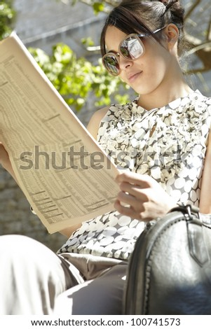 Young businesswoman reading a financial newspaper in a park, wearing sunglasses. - stock photo