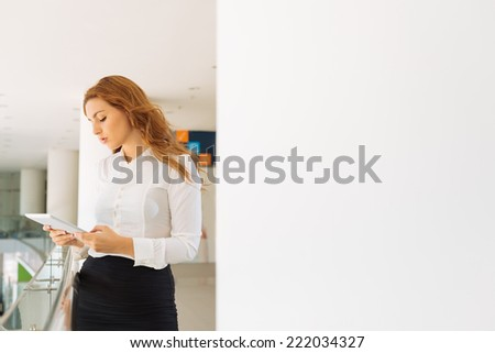 Young businesswoman reading on a tablet computer - stock photo