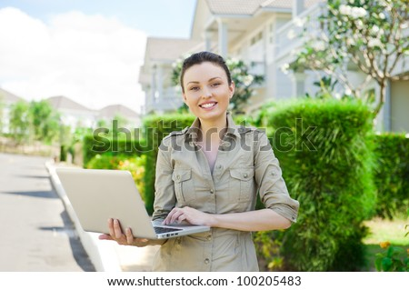 Young businesswoman (real estate agent) holding a laptop and presenting detached family house - stock photo