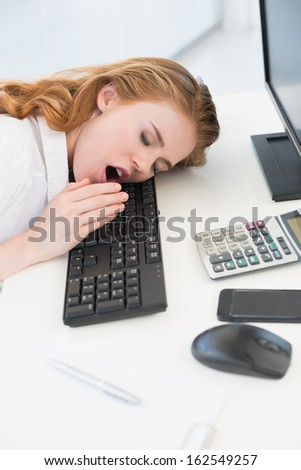 Young businesswoman resting head on keyboard while yawning in the office - stock photo