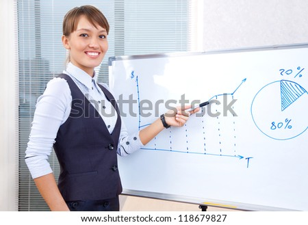 young businesswoman showing graph on chart in office - stock photo