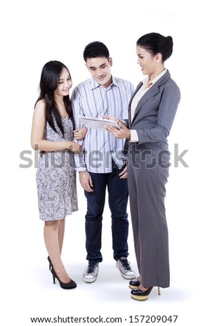 Young businesswoman showing her product on a tablet - stock photo