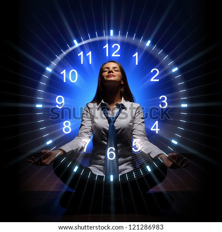 Young businesswoman sitting against blue background with clock interface - stock photo