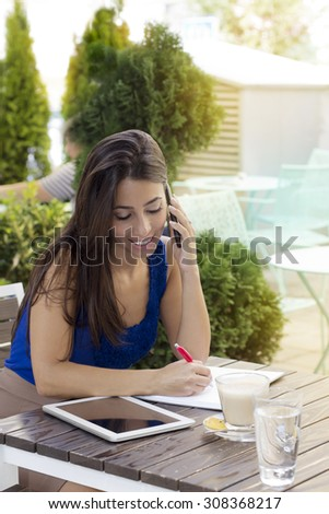 Young businesswoman sitting  at a desk sitting in a cafe and using a smart phone outdoors. - stock photo