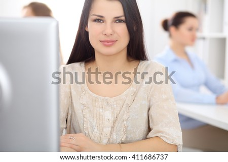 Young businesswoman sitting at desk and working - stock photo