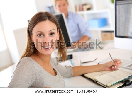 Young businesswoman sitting at desk in office - stock photo