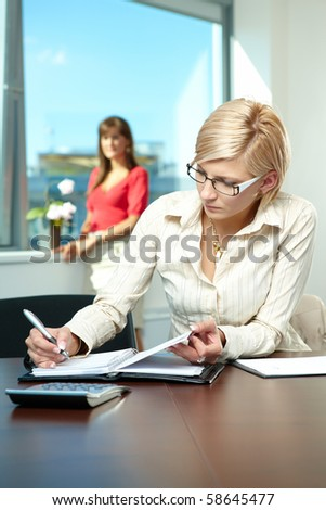 Young businesswoman sitting at desk in office, writing notes to personal organizer. - stock photo