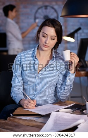 Young businesswoman sitting at desk, writing, drinking coffee. - stock photo