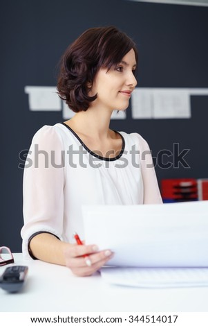 Young Businesswoman Sitting at her Desk with Documents Looking to the Right Side of the Frame. - stock photo