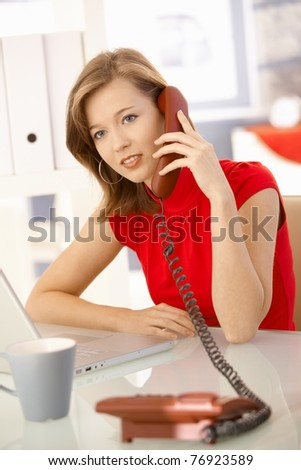 Young businesswoman sitting at office desk, talking on landline phone. Looking at camera.? - stock photo