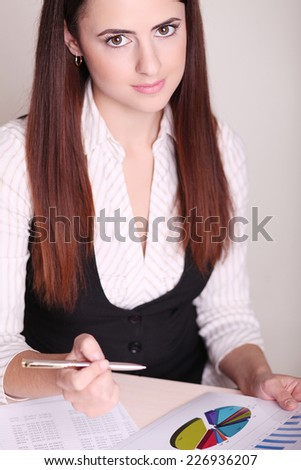 Young businesswoman sitting at workplace and reading documents in office  - stock photo